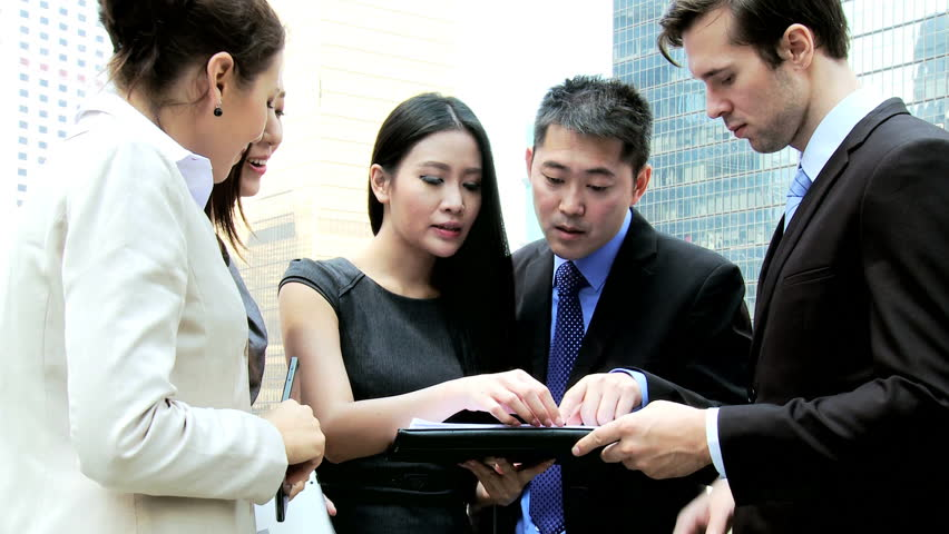 Confident young male female multi ethnic business colleagues meeting talking mini tablet data outside downtown office building | Shutterstock HD Video #6646706