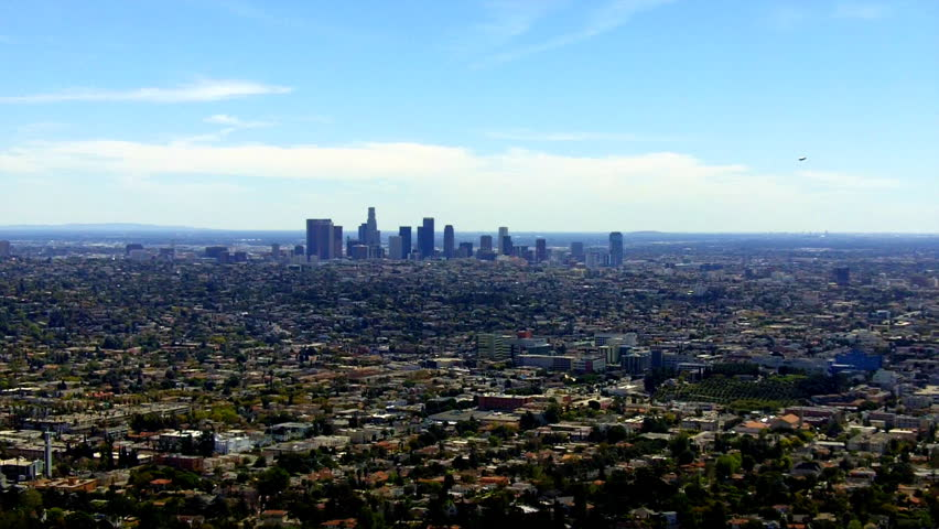 High and wide view of the Los Angeles city to downtown skyscrapers. This clip features the expanse of the city's populated looking landscape from a high vantage point.    Shutterstock HD Video #6670838