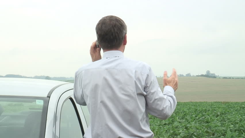 HD 1080i: Annoyed businessman talking on cell phone beside his car.