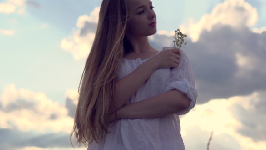 Beauty romantic girl on summer field. Beautiful young woman over cloudy sky enjoying nature and smelling wild flowers. Slow motion video footage full HD 1080. High speed camera shot 240 fps   Shutterstock HD Video #6681668