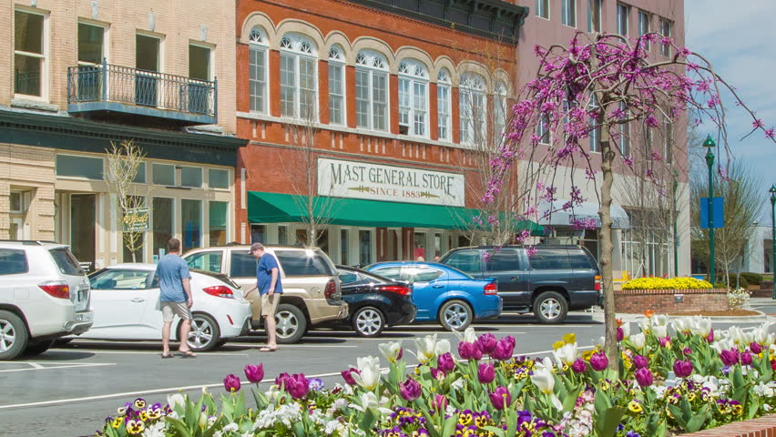 HENDERSONVILLE NC - 2014: Main Street Shops in Historic Downtown Hendersonville North Carolina with Colorful Tulips during Spring Season with parked Vehicles on a Day of Sunshine in WNC.