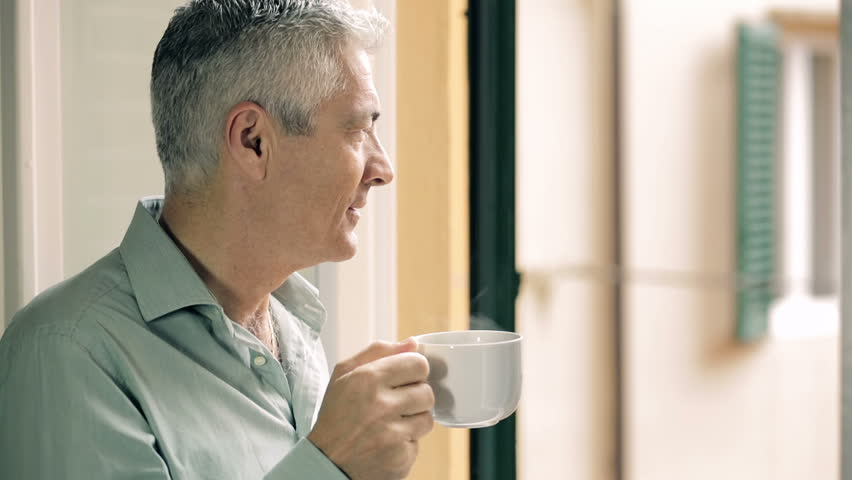 Pensive man drinking coffee at the window: thinking, look, hot, old | Shutterstock HD Video #6706435