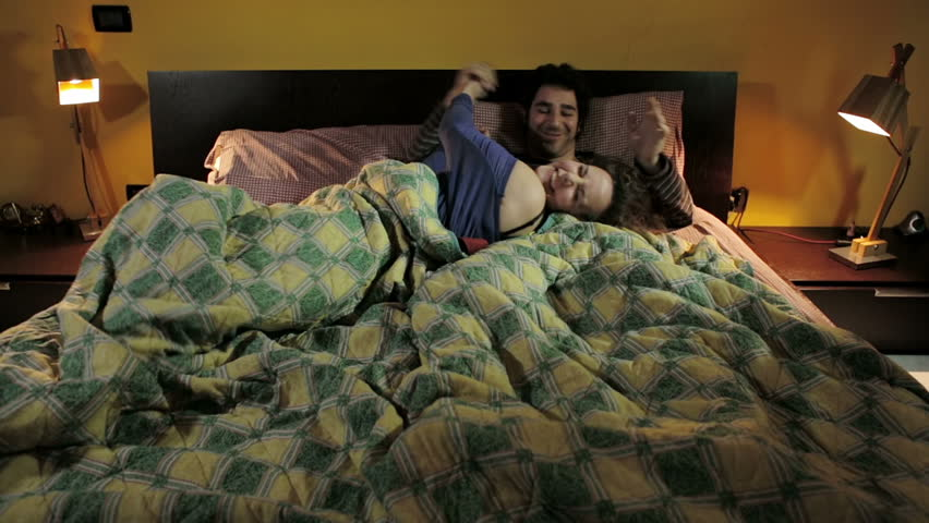 couple flirting in bed: joke, play, have fun, sexuality, love, living together