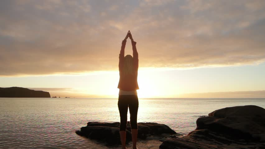 Young woman practicing yoga on the beach at sunset   Shutterstock HD Video #6731728