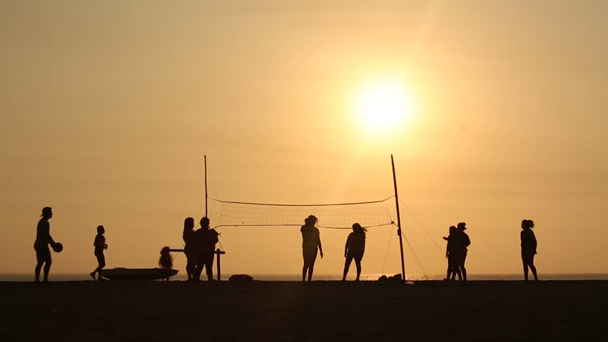video footage people playing Beachvolleyball in the sunset