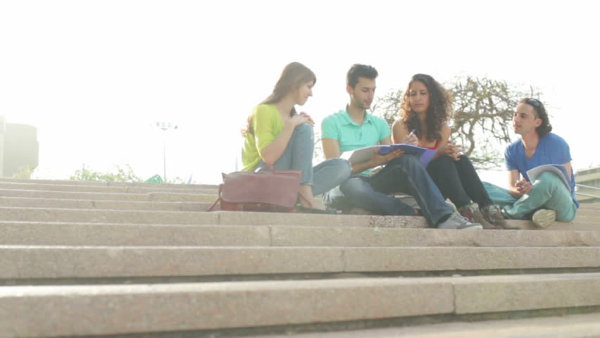 Dolly day shooting of four young people sitting on stairs outdoors and working on project Royalty-Free Stock Footage #6791131