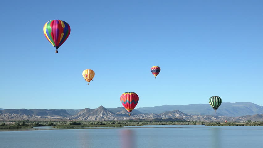 SALINA, UTAH - JUN 2014: Colorful hot air balloon flight over rural lake. Pilot fly slow moving aircraft. Early morning community festival has annual Balloon Fest and competition. Mountain valley.