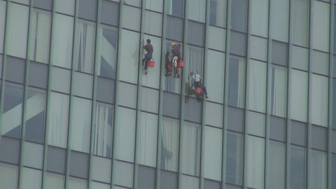 Modern climbing workers hanging in ropes cleaning business glass building danger