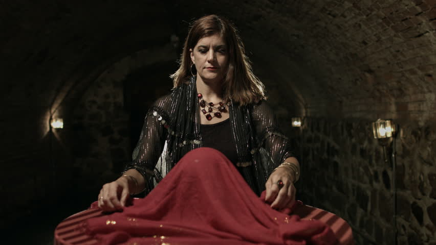 Fortune teller reveals a crystal ball in a medieval style stone cellar.  Wide shot with jib move.  UHD 4K.   Shutterstock HD Video #6850243