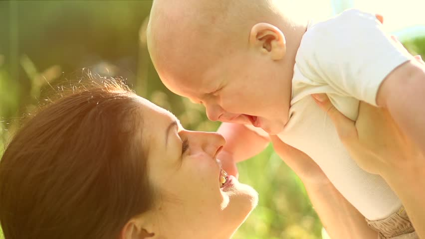 Mother and Baby having fun Outdoors.Together in Green Summer Park. Mom and Child. Happy Family Smiling. Beautiful family in spring park enjoying nature. Slow motion 1920x1080
