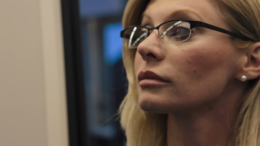 Female commuter uses digital tablet on train, seen reflected in her glasses | Shutterstock HD Video #6857971