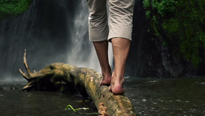 Man walking on wood log by waterfall  #6879442