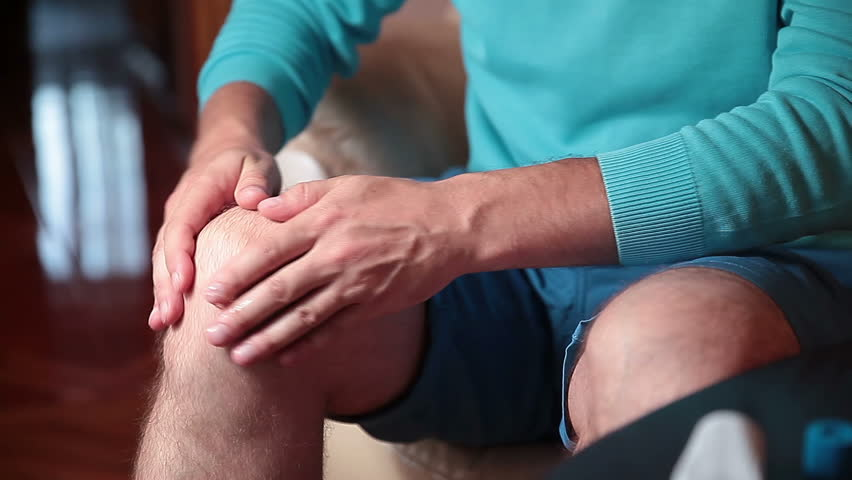Man smears cream and massages injured knee.