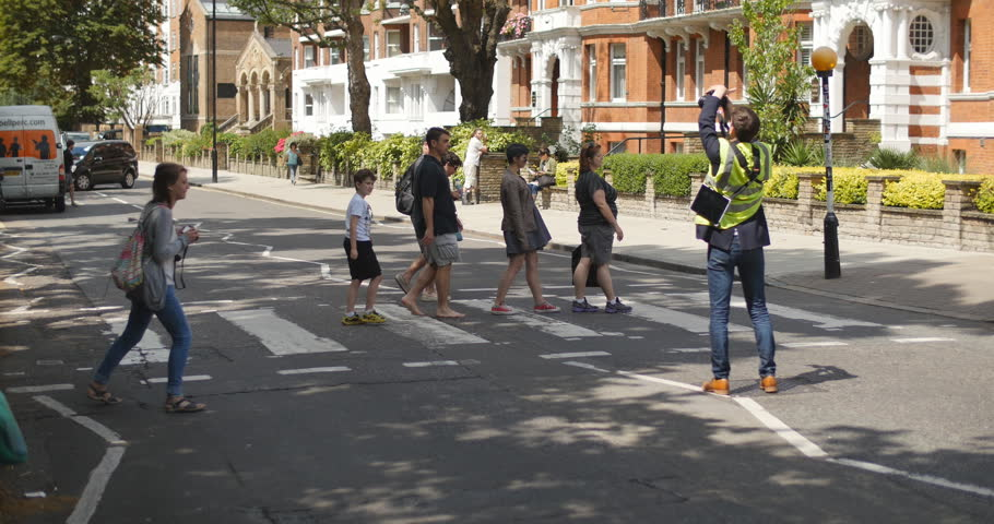 LONDON - CIRCA JULY 2014: Family on vacation have iconic picture taken at Abbey road
