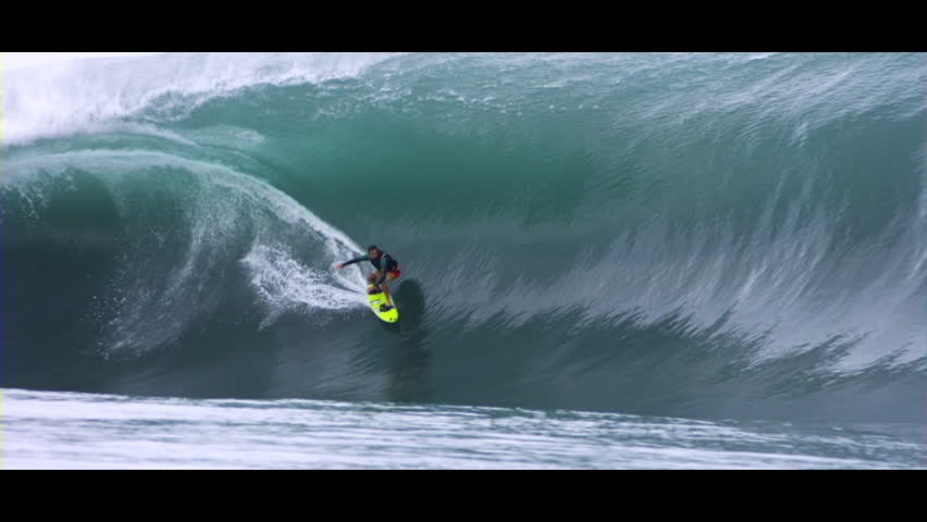 Surfer riding a huge wave using the regular foot technique, slow motion
