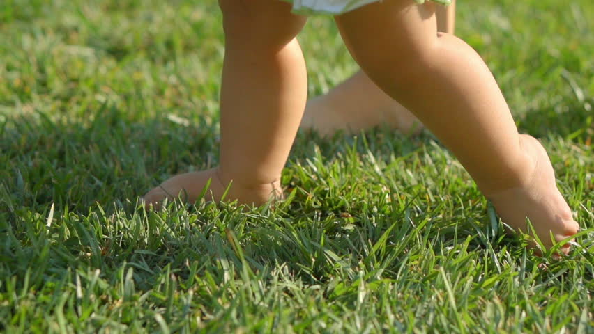 Little baby learns to walk. Mother is teaching her child to do the first steps on a green grass in summer. Close up on feet. Slow motion filmed at 250 fps.  #6957661