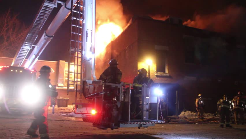 Montreal, Canada - February 2014 - Firetruck elevated platform rising with fire in backgroundA ladder platform linked to a fire truck with two firemen inside is rising slowly with building on fire