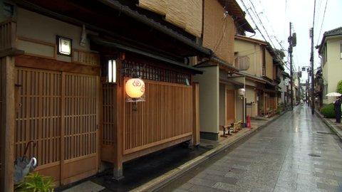 Osaka, Japan - April 2013: Long shot of Osaka back street during a wet morning. Woman dressed in Kimono enters building