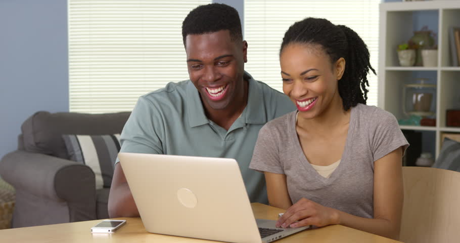 Happy young black couple laughing and using laptop together | Shutterstock HD Video #6987499