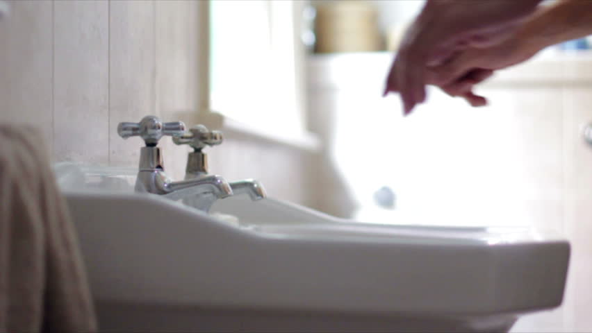 Young male freshens up by washing his hands and face in the sink of the bathroom, at half speed Royalty-Free Stock Footage #6994132