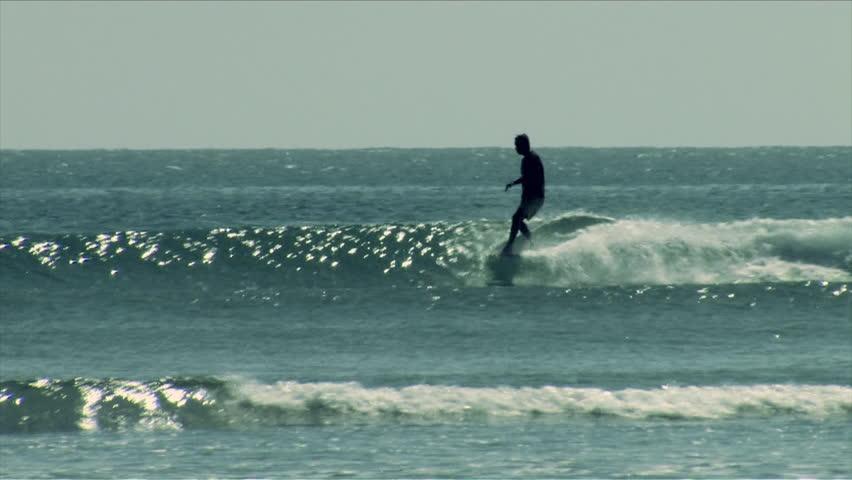 A surfer does a hang ten on a longboard   Shutterstock HD Video #7025806