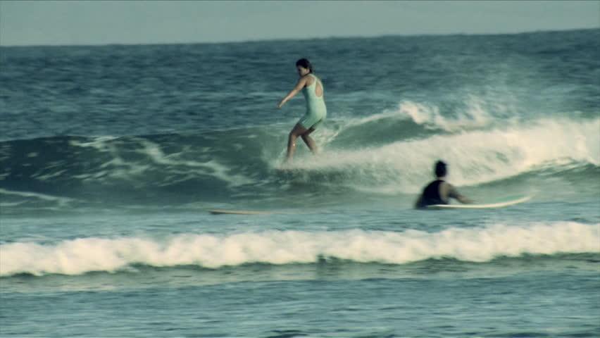 A surfer does a hang five on a longboard   Shutterstock HD Video #7025812