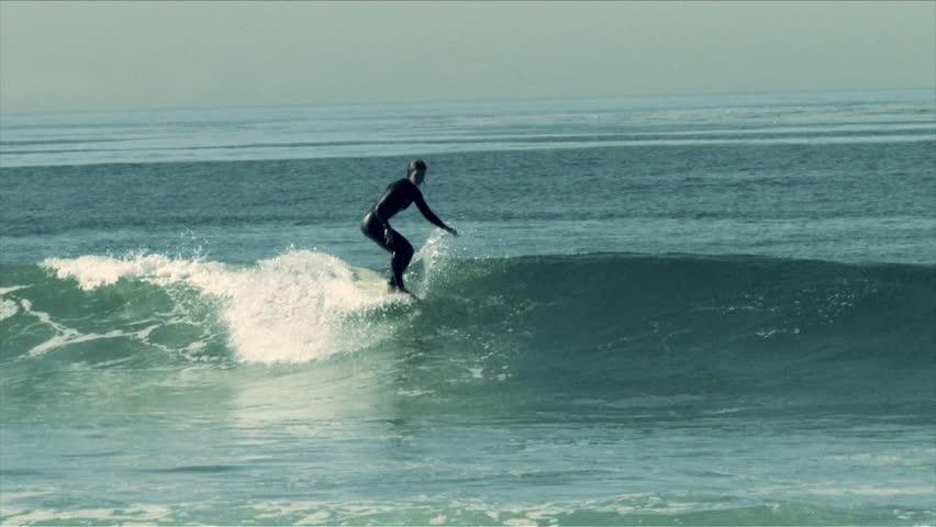 A surfer does a hang five on a longboard   Shutterstock HD Video #7025851