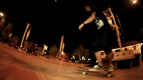 Skateboarder grinds on a rail in a skate park by night