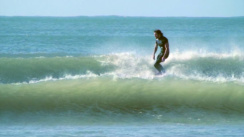 A surfer nose riding on a longboard whilst hanging ten   Shutterstock HD Video #7032931
