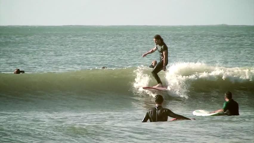 A surfer does tricks on a longboard   Shutterstock HD Video #7032955