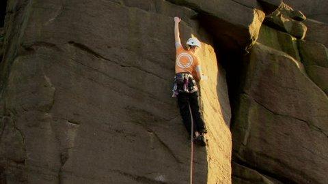 A female e rock climber climbs up a steep rock