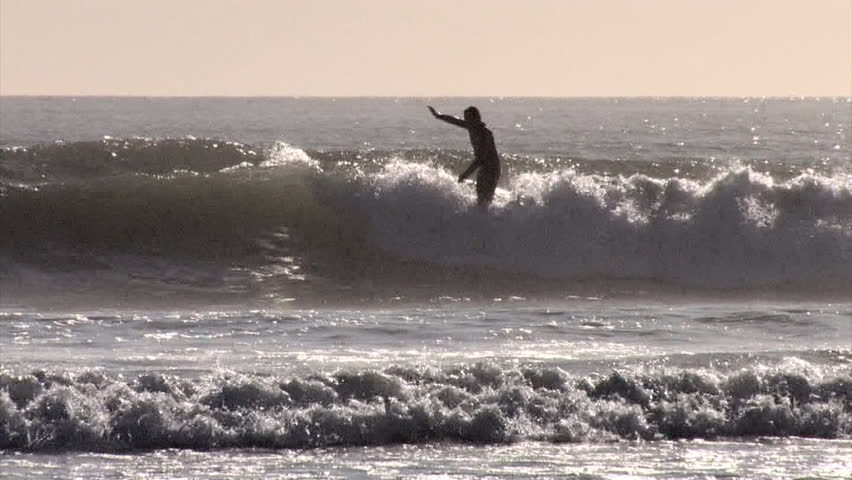 A surfer nose rides on a longboard whilst hanging ten   Shutterstock HD Video #7047796