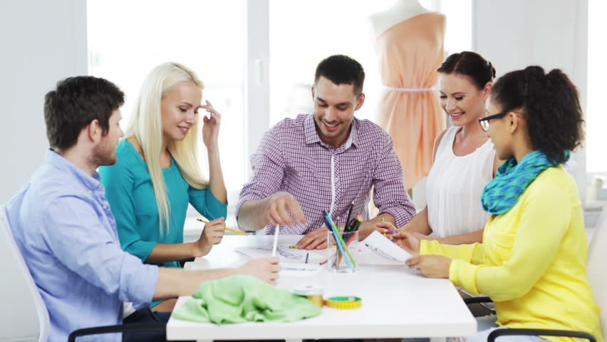 Startup, fashion, teamwork and office concept - smiling fashion designers working in office | Shutterstock HD Video #7049482