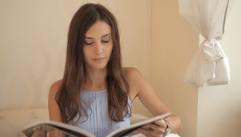 Pretty Caucasian woman reading a magazine at home. Next she is using mobile phone.   Shutterstock HD Video #7065289