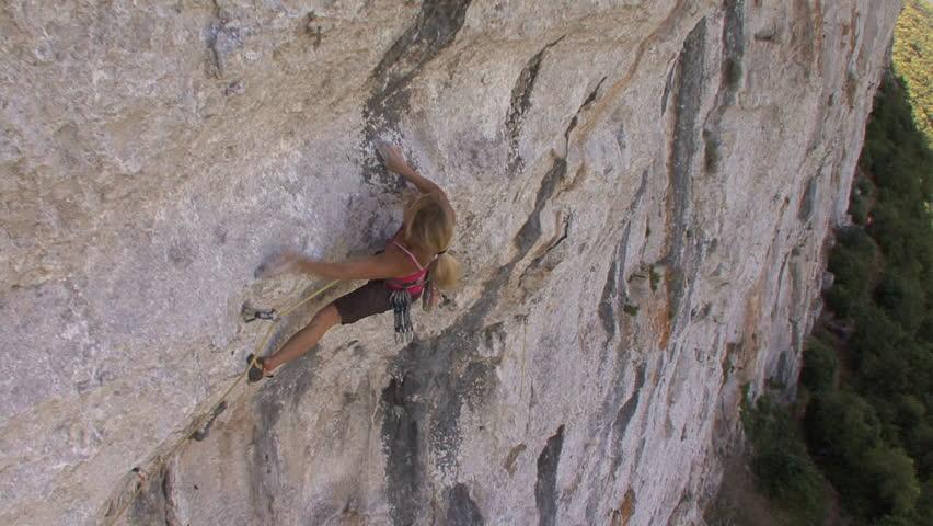A female climber climbs up a steep rock #7065826