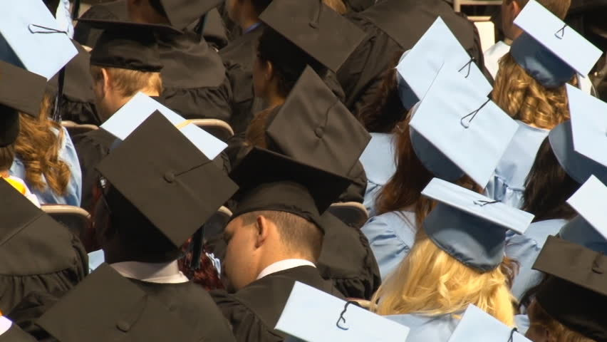 High angle shot from behind seated graduates during indoor ceremony. | Shutterstock HD Video #7073233