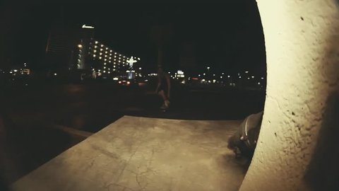 A skateboarder skateboarding at night, uses his right leg to gain some momentum, POV
