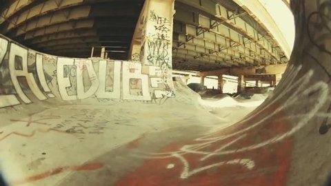 A skateboarder skateboarding in a halfpipe, POV