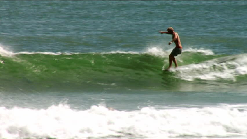 A surfer carves while riding a wave, loses balance and falls into water   Shutterstock HD Video #7095085
