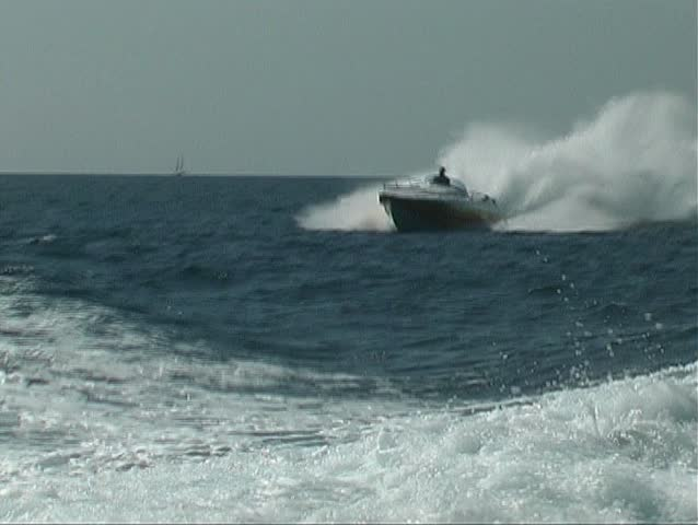 Speedboat jumping over the backwash from a motor yacht
