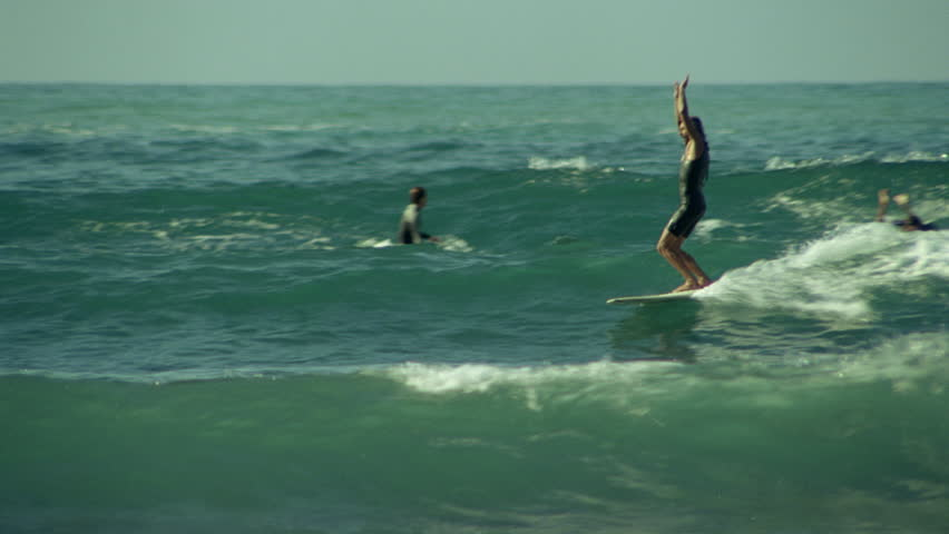 A surfer performs the soul arch while riding a wave   Shutterstock HD Video #7095475