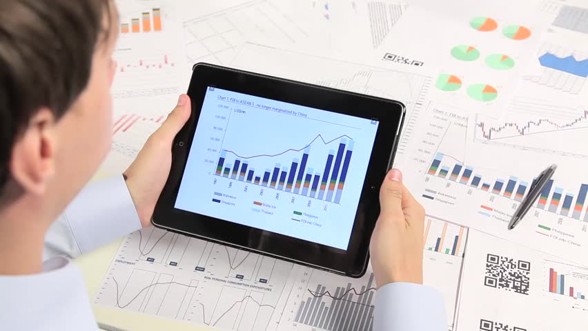 Business people developing a business project and analyzing market data information on a modern digital tablet computer | Shutterstock HD Video #7104133