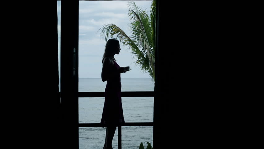 Silhouette of woman drinking coffee on terrace with view at sea  | Shutterstock HD Video #7116040