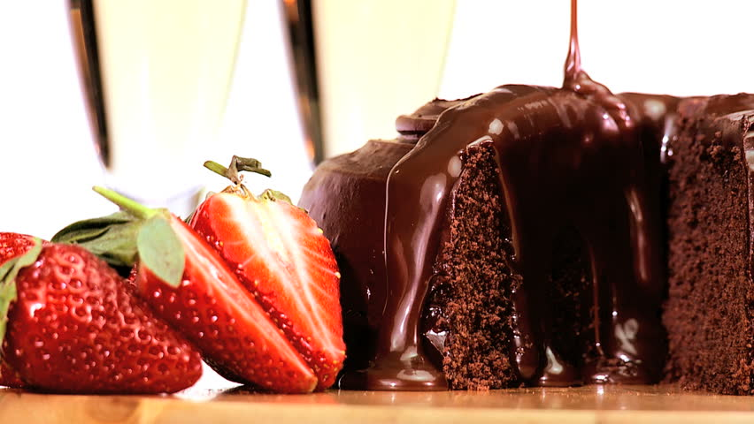 Sticky chocolate cake being covered in sauce while served with fresh strawberries & sparkling white wine