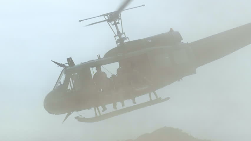 Huey helicopter taking off, with riders, the desert