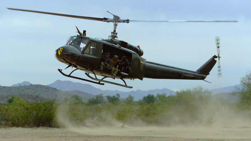 Huey helicopter flies and lands in the desert.
