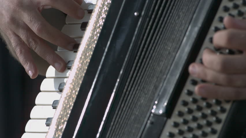 Close up on hands playing accordion in slow motion.