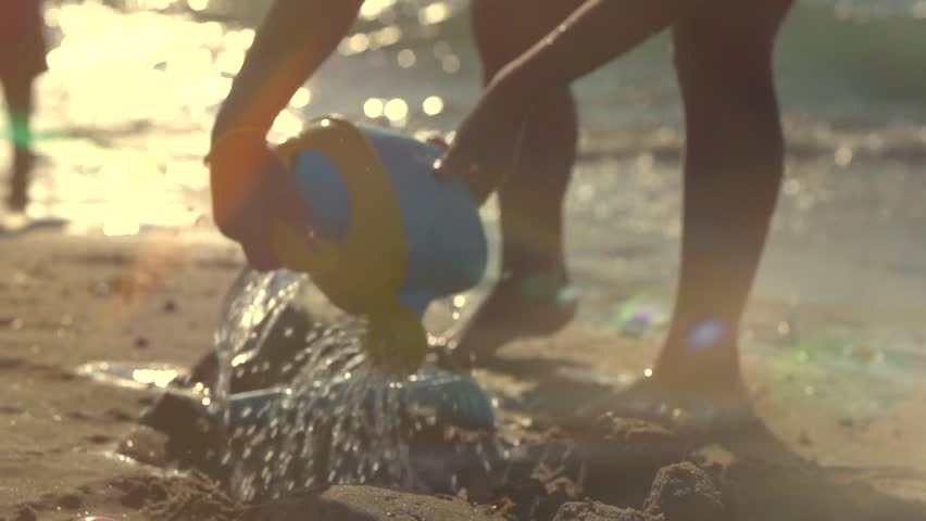 A Little Girl Having Fun with a Sand and Sear water. Silhouette of a Child Playing with Toys on the Seashore. Funny little girl Making a Sand Castle on a Sandy Beach. Slowmotion full HD 1080p 240 fps #7139005