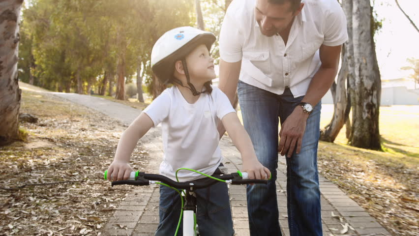 Steadicam shot of father teaching son how to ride his bike on a park pathway with safety helmet. #7140856