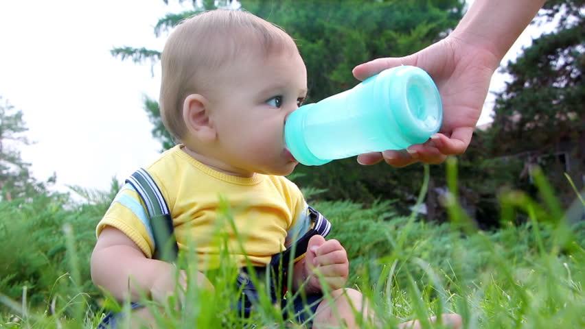 Cute little baby boy drinking water from feeding bottle outdoors #7181866